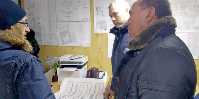 Участники совещания собираются  вокруг чертежей строящегося молзавода